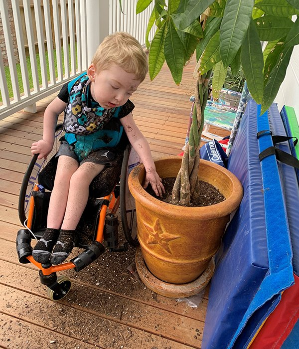 A photo of Levi Hoot in his wheelchair digging in a potted plant. Photo credit: Nathan Hoot, MD.