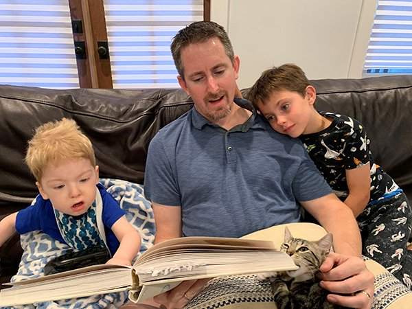 Nathan Hoot, MD, reads to his two sons on the couch. Photo credit: Nathan Hoot, MD.