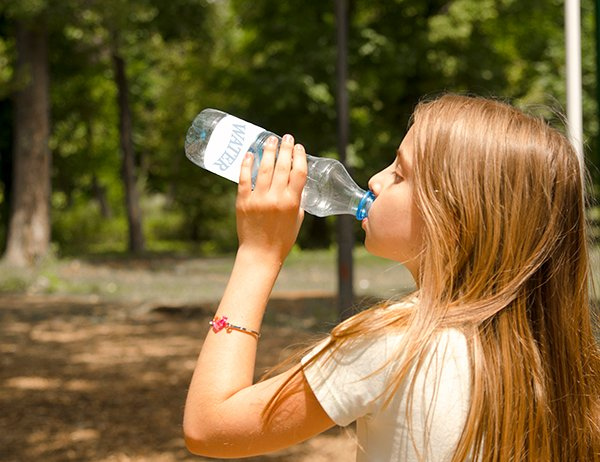 Photo of girl drinking a bottle of water. Photo credit is Getty Images.